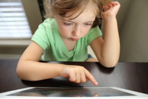 iPadで勉強する少女